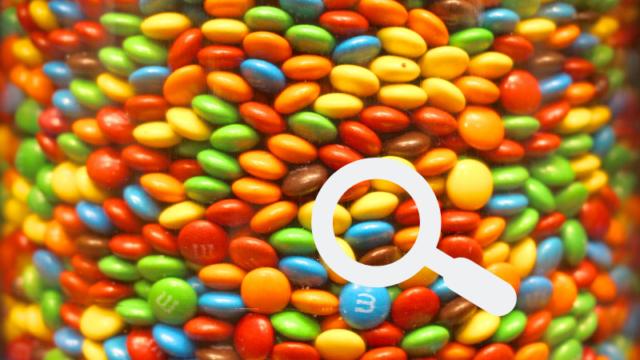 マーブルチョコの詰まった瓶の中から、どれにするか一粒虫眼鏡で選んでいる写真