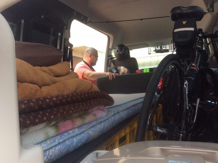 自転車やポータブルトイレなど車中泊に必要なものを積んだNV350キャラバンの写真